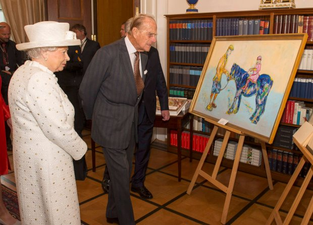 Britain's Queen Elizabeth and Prince Philip look at a painting presented to her during a visit to Germany's President's official residence, in Berlin, Germany, June 24, 2015. REUTERS/Arthur Edwards /Pool