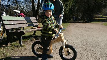 Niespełna dwuletni Ignaś uczy się jeździć na rowerku biegowym.