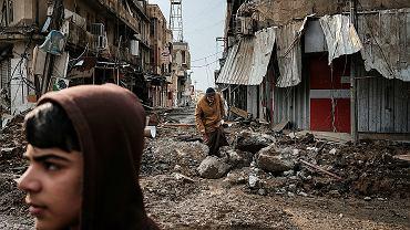 Ulica bomb. Mosul, Irak, styczeń 2017. Mężczyzna omijający lej po bombie w dzielnicy, z której wyparto ISIS