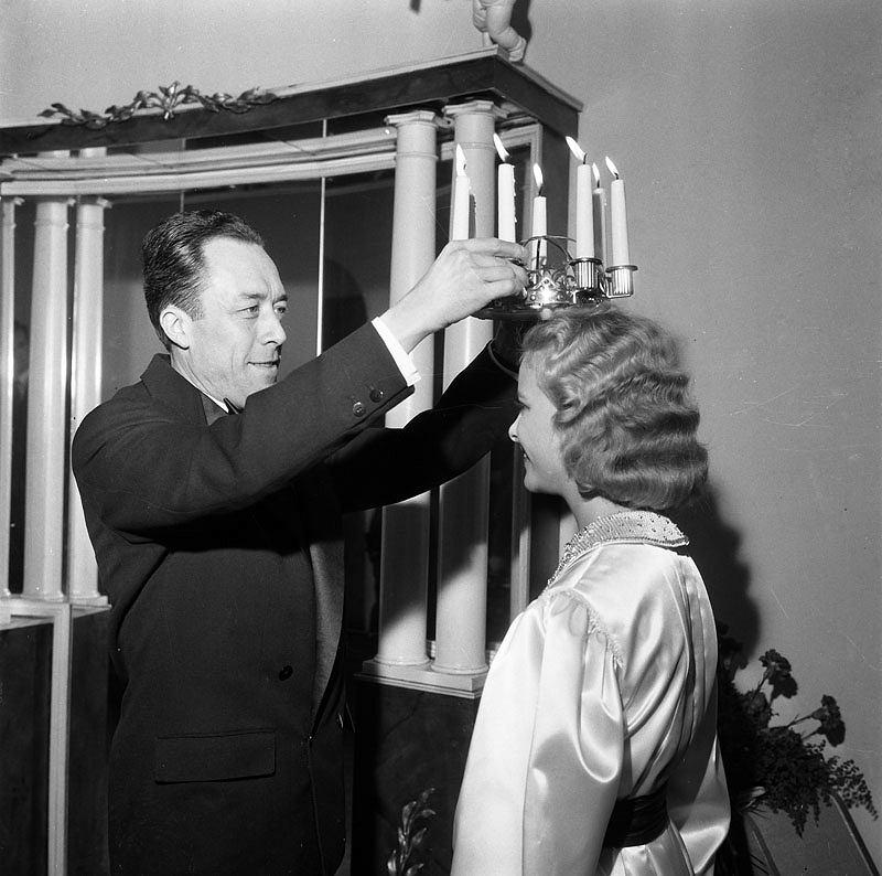Albert Camus koronuje kobietę wybraną do roli św. Łucji w Sztokholmie w 1957 roku / Domena publiczna