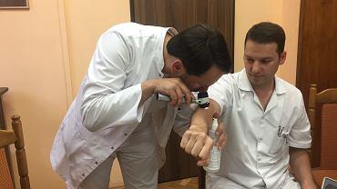Jacek Calik i dr Marcin Ziętek demonstrują jak wygląda badanie dermatoskopem