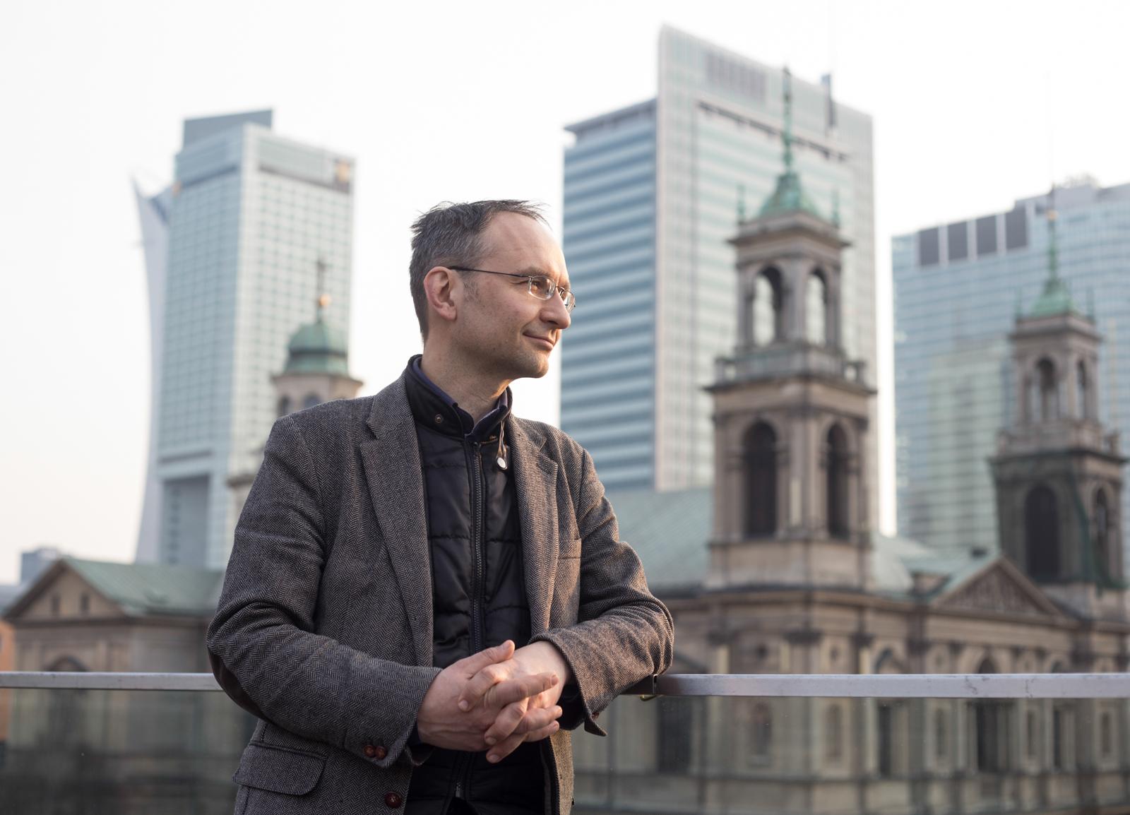 Wojciech Popławski na dachu jednej z kamienic, w tle między innymi współprojektowany przez niego Hotel InterContinental (fot. Luka Łukasiak)
