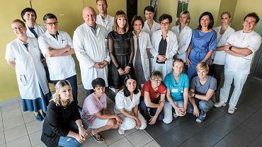 Sylwia Krzyżycka (stoi w środku grupy w ciemnej sukience) z zespołem lekarzy, pielęgniarek, rehabilitantów i psychologów z Kliniki Chirurgii Głowy, Szyi i Onkologii Laryngologicznej w Wielkopolskim Centrum Onkologii. Obok niej, ze strony jej prawej ręki, stoi szef kliniki, prof. Wojciech Golusiński