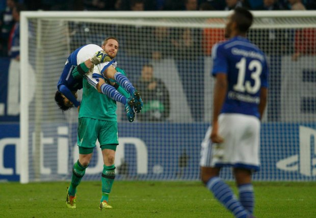 Schalke 04s goal keeper Faehrmann celebrates with Uchida following their victory over Sporting in their Champions League group G soccer match in Gelsenkirchen