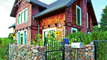 Dom Katarzyny i Kaja, otoczony słonecznikami, wrósł w sielski krajobraz mazowieckiej wsi. Uwagę zwraca oryginalna bryła z dwuspadowym dachem oraz gabiony wypełnione polnymi kamieniami.