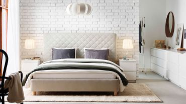 Wysoki pikowany zagłówek oddziela łóżko od ceglanej ściany /IKEA