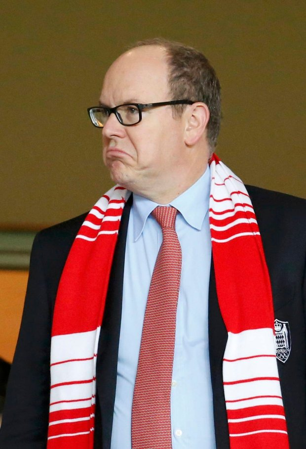 Monacos Prince Albert makes a face as he wears his Monaco club scarf ahead of their Champions League soccer match against Benfica at the Louis II Stadium in Monaco