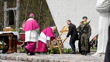 Prezydent Andrzej Duda podnosi przewrócony przez wiatr stelaż z obrazem Matki Boskiej