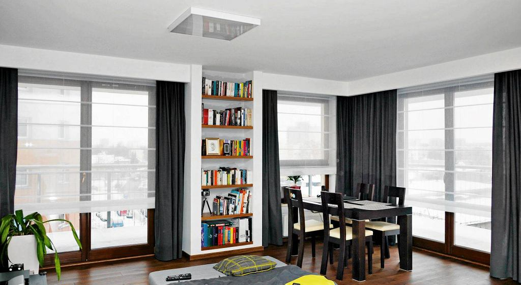DEOKORACJE OKIEN. We wnęce, która powstała po okoleniu pokoju listwami zasłaniającymi szyny do zasłon i rolet, znajduje się regał na książki. Zbudowano go z płyty gipsowo-kartonowej i wypełniono półkami z litego drewna.