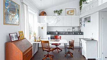 Otwarta kuchnia jest częścią strefy dziennej. Są w niej proste białe szafki (zrobione przez firmę zMławy) oraz meble, które pasują stylem również do salonu: krzesła biurowe zAmeryki ibiała szafka ztargu staroci. Na podłodze - dąb olejowany. Blat ipas kamienia na ścianie to chiński granit. Sposób na oszczędności: stół to pomalowana na biało płyta OSB, do której przykręcono metalowe nogi z dawnego biurka córki.