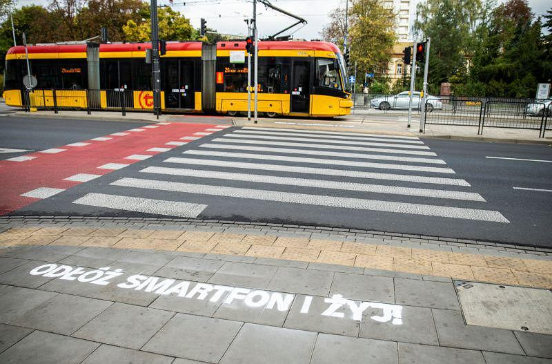 Hasło Odłóż smartfon i żyj przy przejściach dla pieszych w Warszawie