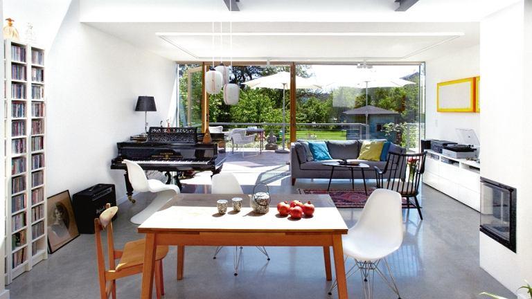 W salonie kolekcja krzeseł: czarne drewniane, po babci Kaspra, przyjechało z Holandii (Lounge chair by Lena Larsson for Nesto, lata 60.); białe Panton i model Charlesa i Ray Eamesów. Obok krzesła ze sklejki z 1956 r. Nad dębowym stołem z Habitatu klosze z lat 60.