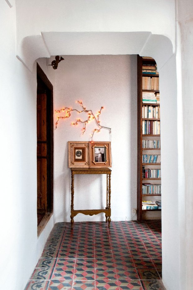 Stare fotografie na stoliku wyszukanym na targu staroci w Casablance, nad nim girlanda z lampkami (Habitat).