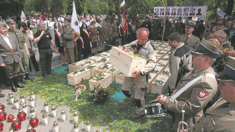 Przenoszenie małych trumien ze szczątkami ofiar stalinizmu z kwatery