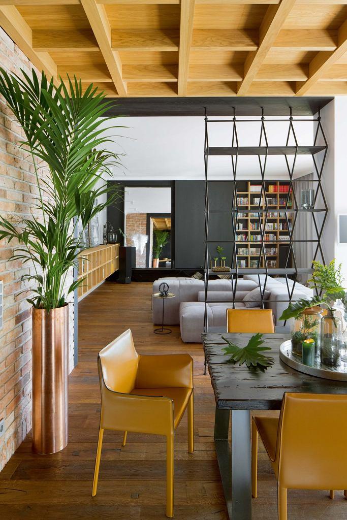 Apartament składał się zkilku niewielkich pokoi. Po wyburzeniu ścianek działowych powstała otwarta przestrzeń. Lustro pod ścianą wsalonie jeszcze bardziej ją powiększa.