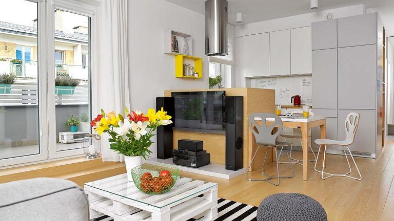 Biel, czerń i szarości - mieszkanie inspirowane stylem skandynawskim rozweselają żółte i czerwone akcenty.