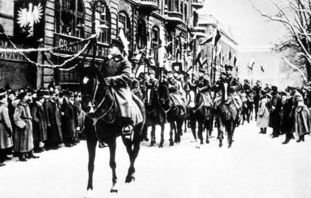 Styczeń 1919 r. Defilada kawalerii powstańczej na placu Wolności (wówczas Wilhelmowskim) w Poznaniu, w tle popularna kawiarnia Grand Café. Z okien zwisają proporce z powstańczym orłem wielkopolskim. 26 stycznia 1919 r. na placu Wolności odbyła się przysięga wojsk powstańczych. 'W obliczu Boga Wszechmogącego w Trójcy Świętej Jedynego ślubuję, że Polsce, Ojczyźnie mojej, i sprawie całego Narodu Polskiego zawsze i wszędzie służyć będę, że kraju ojczystego i dobra narodowego do ostatniej kropli krwi bronić będę, że Komisarzowi Naczelnej Rady Ludowej w Poznaniu i dowódcom, i przełożonym swoim mianowanym przez Komisariat zawsze i wszędzie posłuszny będę. Że w ogóle tak zachowywać się będę, jak przystoi na mężnego i prawego żołnierza-Polaka, że po zjednoczeniu Polski złożę przysięgę żołnierską ustanowioną przez polską zwierzchność państwową' - przysięgali powstańcy