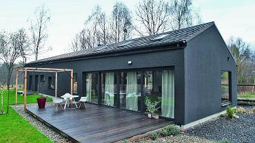 Dom ma nietypowy kształt i równie niebanalny kolor - otynkowano go na grafitowy odcień. Od wiosny do późnej jesieni życie rodzinne i towarzyskie przenosi się na taras z modrzewiowych desek.