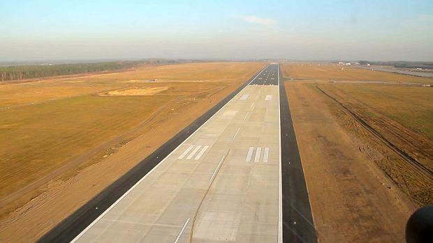 Lotnisko w Modlinie - lato 2012. Wida� wyra�nie betonow� i asfaltow� cz�� pasa startowego