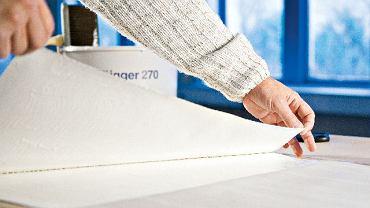 Krok 1. Bryt tapety rozwijamy na stole i rozprowadzamy na nim klej. Tapetę składamy tak, aby jeden jej koniec (około 20 cm od krawędzi) pozostał wolny, i smarujemy go klejem.
