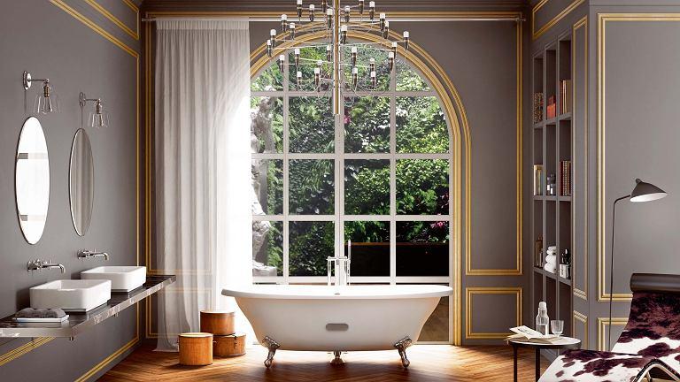 Mariaż łazienkowych sprzętów i elementów kojarzących się z salonem: ozdobnej stolarki na ścianach, parkietu ułożonego w jodełkę, żyrandola oraz szezlonga. Jednak główną bohaterką tego wnętrza jest stylowa wanna Newcast, Roca.