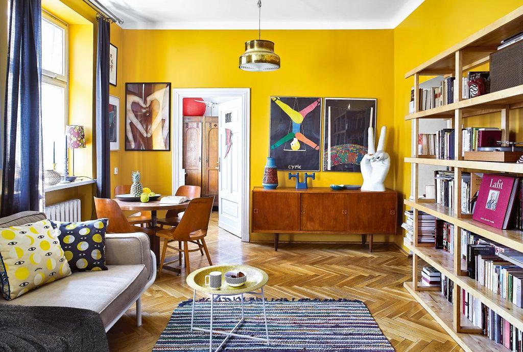 Mocne kolory, oryginalne meble i plakaty polskich artystów - pokój dzienny nawiązuje stylem do lat sześćdziesiątych XX wieku. Charakterystyczną komodę na zwężających się nóżkach gospodyni znalazła na Allegro.