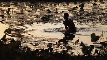 Mężczyzna kąpiący się w stawie na przedmieściach Phnom Penh, styczeń 2015