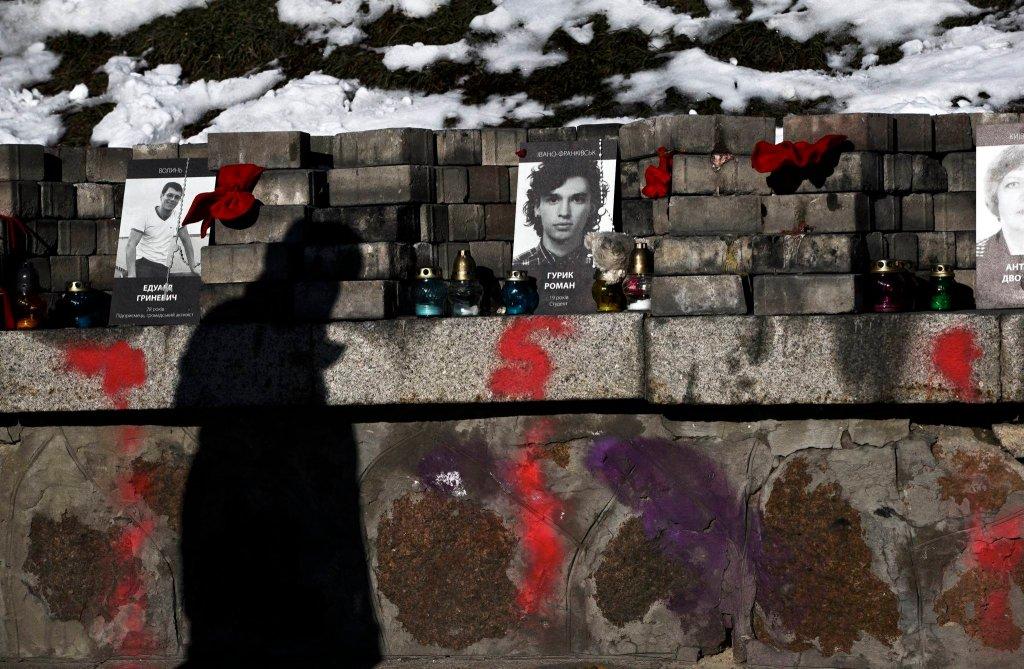 Cień mężczyzny przed murem pamięci na kijowskim Majdanie