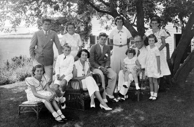 A portrait of the Kennedy family as they sit in the shade of some trees, Hyannis, Massachussetts, 1930s. Seated from left are: Patricia Kennedy (1926 - 2006), Robert Kennedy (1925 - 1968), Rose Kennedy (1890 - 1995), John F Kennedy (1917 - 1963), Joseph P Kennedy Sr (1888 - 1969) with Edward Kennedy on his lap; standing from left are: Joseph P Kennedy Jr (1915 - 1944), Kathleen Kennedy (1920 - 1948), Rosemary Kennedy (1918 - 2005), Eunice Kennedy (rear, in polka dots), and Jean Kennedy. (Photo by Bachrach/Getty Images)