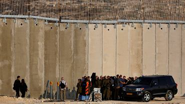 Israeli Prime Minister Benjamin Netanyahu and Defence Minister Avigdor Lieberman are surrounded by their security personnel and entourage after a media briefing near an Israeli barrier with the West Bank which is still under construction near Havat Ela