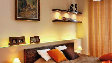 Najważniejszym zadaniem oświetlenia w sypialni jest stworzenie atmosfery do odpoczynku i wyciszenia się przed snem. Planując źródła światła, nie zapominajmy jednak o oświetleniu funkcjonalnym, niezbędnym na przykład do ubierania się lub czytania.  <BR /> OŚWIETLENIE SYPIALNI. OŚWIETLENIE OGÓLNE Lampy wiszące z efektownymi abażurami i dekoracyjne żyrandole są jednocześnie ozdobą. Powinny wisieć w takim miejscu na suficie, by nie raziły w oczy osób leżących w łóżku. <BR /> OŚWIETLENIE DEKORACYJNE Funkcję tę pełnią zwykle diody LED instalowane np. w ściance za wezgłowiem albo w podwieszonym suficie. Podobną rolę odgrywają halogeny (tutaj zainstalowano je pod jedną z półek). <BR /> LAMPKI NOCNE Przydają się, gdy np. wstajemy w nocy. Jeśli mają służyć także do czytania, ich światło powinno padać na książkę (w tej roli lepiej sprawdzą się kinkiety lub reflektorki, np. na klipsie, mocowane do zagłówka).