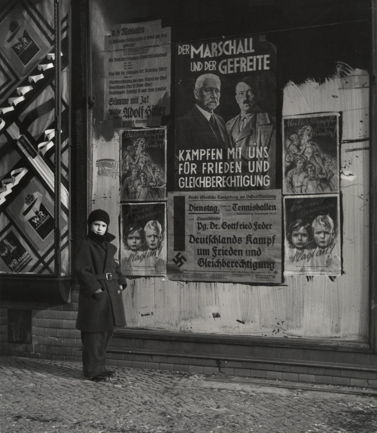 """Córka Vishniaca, Mara, pozuje przed plakatem wyborczym Hindenburga i Hitlera, na którym widnieje napis: """"Marszałek i Kapral: Walczcie z nami o pokój i równouprawnienie"""", Wilmersdorf, Berlin], 1933. (fot.   Mara Vishniac Kohn, dzięki uprzejmości  International Center of Photography)"""