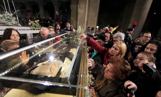 Faithful surround the exhumed body of the mystic saint Padre Pio in a glass, as arrives at the Catholic church of San Lorenzo fuori le Mura in Rome, February 3, 2016. The body of one of the most popular Roman Catholic saints, the mystic monk Padre Pio began an overland journey in a crystal coffin on Wednesday to go on display at the Vatican.    REUTERS/Yara Nardi SLOWA KLUCZOWE: :rel:d:bm:GF10000294587