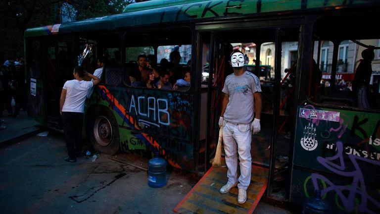 Protestujący przy spalonym autobusie