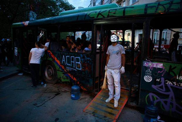 Protestuj�cy przy spalonym autobusie