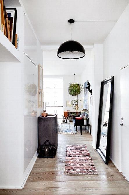 Zawieszona w korytarzu lampa Skygarden Marcela Wandersa (Flos) nawiązuje dialog z ażurową kulą Random Light autorstwa Bertjana Pota (Moooi) wiszącą w salonie.