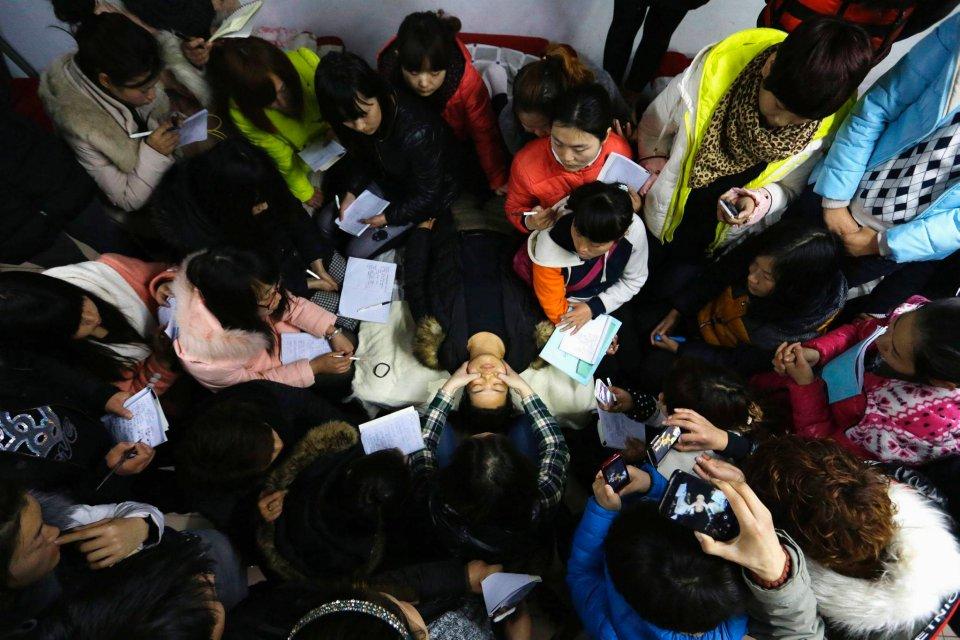 Wang Feng (w środku z prawej) wraz z innymi kursantkami obserwuje, jak ich nauczyciel wykonuje masaż.