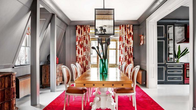 Choć meble zdają się być z różnych bajek (zasłony z tkaniny marki Pierre Frey z orientalnym motywem, stół nabijany ćwiekami, 'pałacowe' krzesła, lustrzany żyrandol), świetnie się dobrały. Dywan jest z firmy Art Relief, kinkiety z showroomu Mesmetric. W głębi drzwi na werandę.