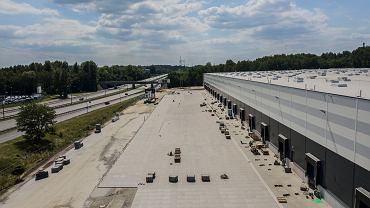 Kończy się pierwszy etap budowy parku magazynowego Hillwood Zagłębie, który powstaje przy ul. Baczyńskiego w Sosnowcu. </p> Hillwood Zagłębie powstaje w miejscu wyburzonego na początku 2017 roku Centrum Handlowego w Sosnowcu. Docelowo powstanie w tym miejscu jedna duża hala magazynowa klasy A o powierzchni  48 tys. m kw. </p> Wewnątrz i na zewnątrz wybudowanej w pierwszym etapie hali [kolejna część zostanie do niej dobudowana] trwają już prace wykończeniowe. Jak informowały wcześniej specjalistyczne portale, jako pierwsza do parku magazynowego wprowadzi się dystrybuująca stal nierdzewną i aluminium firma Investa, która wynajęła przy ul. Baczyńskiego ponad 5 tys. m kw. </p> Jak już wielokrotnie pisaliśmy, otwarte w sierpniu 2001 r. Centrum Handlowe Sosnowiec zostało zamknięte po 15 latach. Zarządcy nie udało się bowiem znaleźć zastępcy dla Reala po przejęciu tej sieci w Polsce przez Grupę Auchan. To był pierwszy przypadek w Polsce, by duże centrum handlowe zostało zamknięte, a następnie wyburzone.