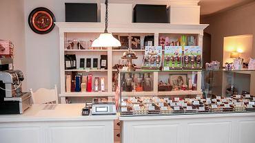 Bą Bą to popularna bydgoska cukiernia z pralinami i czekoladą, sprowadzanymi w Belgii. Od 2014 r. działał przy ul. Gdańskiej. W lipcu właścicielka przeniosła go na ul. Cieszkowskiego. - Do przeprowadzki zainspirował mnie klimat ulicy, jej architektura. Są przy niej przyjemne miejsca i mieszkają miłe osoby - opowiada Angelika Makowska, właścicielka sklepu. - Oprócz tego zauważyłam, że ulica Cieszkowskiego ma bardziej turystyczny charakter niż ulica Gdańska. Przychodzą grupy ludzi, które są zachwycone ulicą. Być może właśnie takie osoby z chęcią zapukają do drzwi Bą Bą. Wystrój w sklepie niewiele się zmienił. Utrzymany jest w jasnych, klasycznych tonach. - Ma być przyjemnie - to jest najważniejsze - mówi Makowska. - Jedyną znaczącą nowością w wystroju Bą Bą będą elementy secesyjne, obrazy nawiązujące do klimatu ulicy Cieszkowskiego. Chcę, by było to miejsce, w którym można zapomnieć o codziennych troskach, porozmawiać. Codziennie rozmawiam z klientami, często osobami, które zawitały do Bą Bą po raz pierwszy. To dla mnie ważne, m.in. dzięki temu uwielbiam swoją pracę. Od września w Bą Bą można spodziewać się nowego, czwartego gatunku czekolady, tzw. 'ruby'. Różowa, produkowana z wyłącznie naturalnych składników, czekolada będzie sprowadzana z Belgii, z jednej z największych firm cukierniczych na świecie. Jesienią w ofercie pojawią się też nowe pralinki od jednego z najlepszych belgijskich 'czekoladników'.