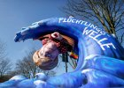 """Poch�d karnawa�owy w Duesseldorfie. Figura przedstawia Angel� Merkel porwan� przez fal�, na kt�rej napisano: """"fala imigrant�w""""."""