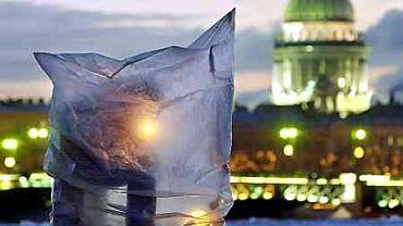 Mężczyzna zapala papierosa siedząc wewnątrz prowizorycznej osłony przed wiatrem i zimnem, w czasie łowienia ryb w przeręblu na Newie. Petersburg 2002