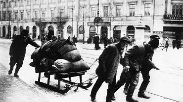 5 sierpnia 1915 r. Niemcy wkroczyli do niebronionej przez Rosjan Warszawy.  Na dolnym zdjęciu niemiecka piechota maszeruje Krakowskim Przedmieściem  na wysokości kościoła Wizytek. Niecały miesiąc później, 1 września 1915 r., w południowej części okupowanego Królestwa Polskiego Austriacy utworzyli Generalne Gubernatorstwo kierowane z Lublina przez gen. Karla Kuka. W północnej części Kongresówki oraz w Zagłębiu Dąbrowskim Niemcy utworzyli Generalne Gubernatorstwo Warszawskie zarządzane przez gen. Hansa von Beselera. Już w październiku 1916 r. w Kongresówce okupant wprowadził kartki na żywność, a pierwsze rozruchy głodowe wybuchły w Warszawie w czerwcu 1916 r