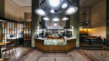 Bar Wykonany z mosiężnych rurek, filary z zielonego kamienia. Kompozycje z bluszczu są pomysłowo zaaranżowane.