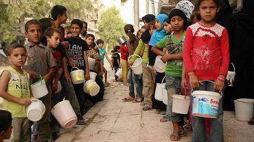 Aleppo, 7 września 2015 r. Syryjskie dzieci stoją w kolejce po żywność i wodę. Z powodu wojny domy musiało opuścić ponad 10 mln Syryjczyków