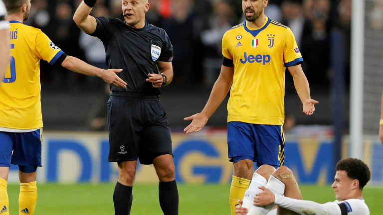 Juventus' Miralem Pjanic receives a yellow card from referee Szymon Marciniak during the Champions League, round of 16, second-leg soccer match between Juventus and Tottenham Hotspur, at the Wembley Stadium in London, Wednesday, March 7, 2018. (AP Photo/Frank Augstein)