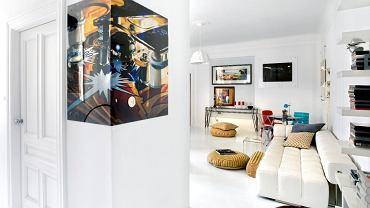 Na narożniku szafy nietypowo zamontowana reprodukcja obrazu 'Pin Ball' Charlesa Bella.  Biała sofa marki Iker, lampa Successful Living marki Diesel Home Collection. Obicia poduch szyte ręcznie przez właścicielkę.