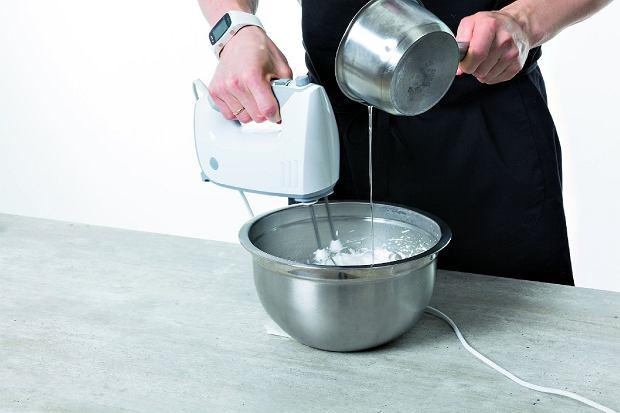 Cały czas ubijając białka, wlewamy bardzo cienkim strumieniem gorący syrop cukrowy.