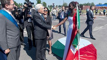 Prezydent Sergio Matarella, wizytujący tereny dotknięte trzęsieniem ziemi, ściska dłoń pięknej czarnoskórej dziewczyny, ubranej w długą, trójkolorową suknię w barwach włoskiej flagi. Nastolatka nazywa się Mbayeb Bousso, pochodzi z Senegalu, żyje i uczy się w Mirandoli, miasteczku na północny kraju.
