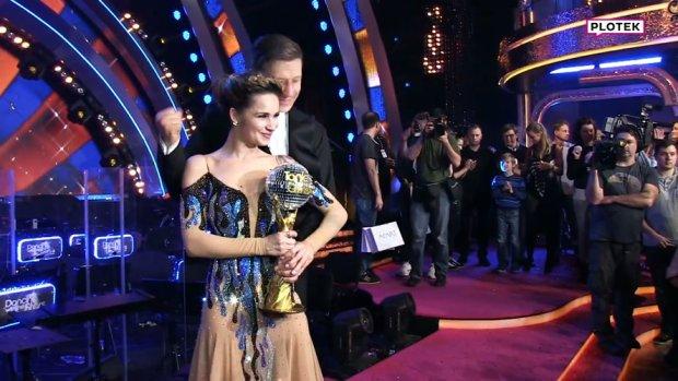 """Tego w historii show jeszcze nie było! Ewelina Lisowska i Tomasz Barański odpadli z programu, wrócili do niego przez kontuzję innej uczestniczki, doszli do samego końca rywalizacji o Kryształową Kulę i ostatecznie wygrali tę edycję """"Tańca z Gwiazdami"""". Piosenkarka w finale zaprezentowała się w kilku """"odsłonach"""". Miała na sobie m.in. opinający ciało kombinezon podkreślający jej niesamowicie zgrabną sylwetkę. Nam bardziej spodobała się jednak piękna suknia odsłaniająca ramiona, w której gwiazda odebrała trofeum."""